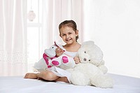 Portrait of little girl with teddy bear in bedroom
