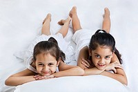 Portrait of cute little sisters lying on bed