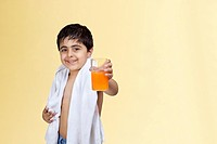 Portrait of smiling boy holding glass of juice over colored background