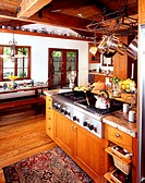 Utensils are hung over the counter while food is being cooked on the gas stove in a spacious kitchen