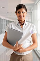 Young businesswoman smiling confidently while holding documents