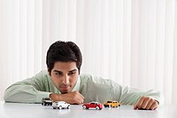 Thoughtful young male executive looking at model cars