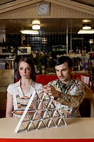 Couple Building House of Cards in a Cafe