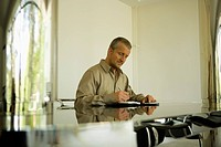 Man Writing on Glass_Topped Dining Table
