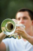 Male caucasian teenager of seventeen years playing trumpet