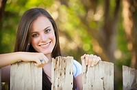 Portrait of female caucasian teenager, 17 years old, behind old wooden fence in Concan, TEXAS, USA