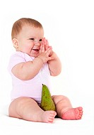 Joyful little girl rejoices to a pear.