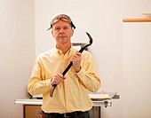 Senior man holding a crowbar