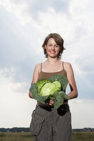 Smiling Woman Holding Cabbage Plant