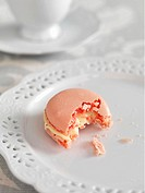 A pink macaroon with a bite taken out