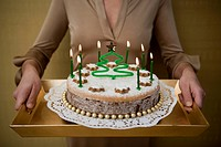 Woman Serving Christmas Cake with Green Candles