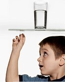 Boy Looking at Drinking Glass Through Table