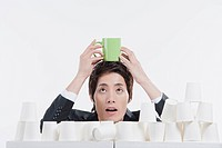 A man holding up green cup with paper cups around