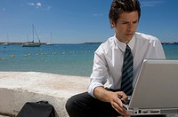 Businessman Using Laptop by Sea