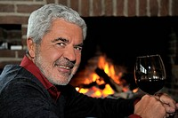 Man Drinking Wine by Fireplace
