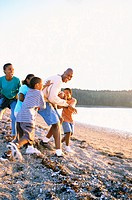 Family Playing Football on Beach