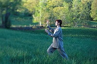 Woman in Meadow Performing Tai Chi