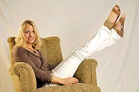 Blonde young woman sitting on couch