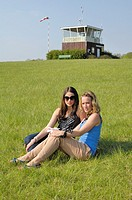 two beautiful sitting on a green meadow in front of a tower for gliders, Salzgitter, Lower Saxony, Germany.