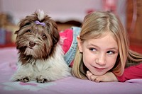 Girl lying next to a Havanese on a blanket