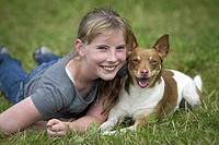Basenji. Girl lying with Basenji_mix on a meadow with both smiling into the camera