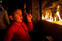 Boy lighting candles, Church of the Holy Sepulchre site of the last five stations of the Cross and venerated as the place where Jesus was crucified an...
