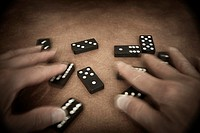 Man´s hands playing with dominoes