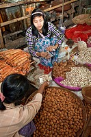 Myanmar, Burma  Customer Buying a Packet of Ginger from Vendor  Bagan Market  Thanaka paste provides a cosmetic sunscreen on the face of the vendor