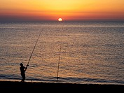Man fishing in the sunset at Capo d'orlando, Siciliy