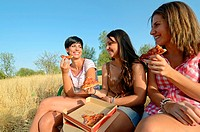 Three young friends eating pizza in the park