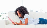 Happy woman reading a novel while lying on her sofa in a bright living room
