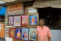 an indian businessman selling religious prints outside his shop in sakinaka district  mumbay  maharashtra  india  asia