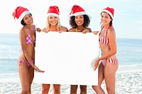 Four women in bikinis presents a large white poster while wearing Santa hats on a beach