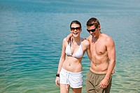 Happy couple in swimwear at sea enjoy sun