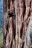 A athletic woman rock climbing near Bozeman, Montana.