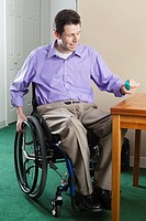 Man in wheelchair with spinal cord injury picking up pill case, quadriplegic issue with hand dexterity