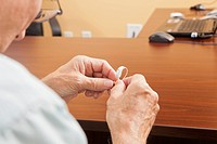Patient adjusting behind_the_ear hearing aid