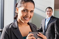 Businesswoman holding tablet with businessman behind her