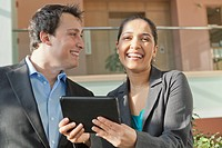 Business couple talking and smiling with a tablet