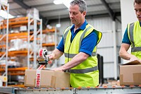 Men packing cardboard box in warehouse