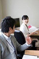 Businessman and businesswoman talking at office