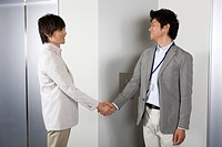 Two businessmen shaking hands at elevator hall