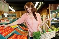 Portrait of a happy brunette shopping for tomatoes in supermarket