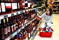 Woman shopping in the beverage section, sparkling wine, champagne, shelves, self-service, Germany, Europe