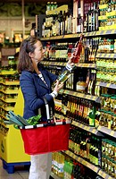 Woman comparing vinegars while shopping in a self-service grocery department, supermarket, Germany, Europe
