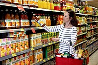 Woman looking at the ingredients of a bottle of juice in the food section while shopping in a self-service grocery department, supermarket, Germany, E...