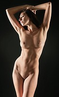 Beautiful young naked woman posing over black background
