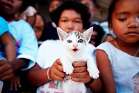 A kitten being held up by a little Thai girl while standing in a group