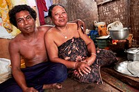 A Thai husband sitting on the floor with his arm around his wife´s shoulder waiting for the food to cook