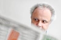 A man reading a newspaper, being astonished, North Rhine-Westphalia, Germany, Europe